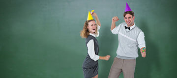 Composite image of geeky couple dancing with party hat Stock Images