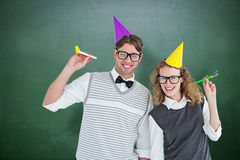 Composite image of geeky couple with party hat and party horn Royalty Free Stock Photography