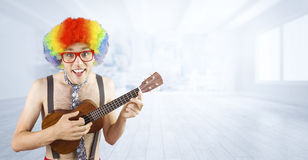 Composite image of geeky hipster in afro rainbow wig playing guitar. Geeky hipster in afro rainbow wig playing guitar against city scene in a room Royalty Free Stock Photo