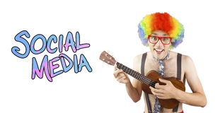 Composite image of geeky hipster in afro rainbow wig playing guitar. Geeky hipster in afro rainbow wig playing guitar against social media Stock Images