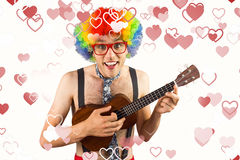Composite image of geeky hipster in afro rainbow wig playing guitar. Geeky hipster in afro rainbow wig playing guitar against valentines heart design Stock Photo