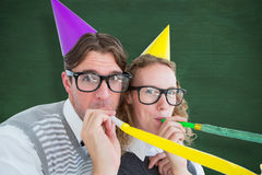 A Composite image of geeky hipster couple blowing party horn Royalty Free Stock Image