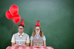 Composite image of geeky hipster couple celebrating his birthday Stock Photography
