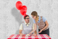 A Composite image of geeky hipster couple celebrating his birthday Royalty Free Stock Images