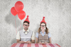 A Composite image of geeky hipster couple celebrating his birthday Royalty Free Stock Photos