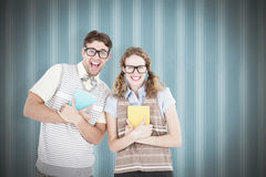 Composite image of geeky hipster couple holding books and smiling at camera Stock Image