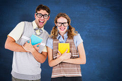 Composite image of geeky hipster couple holding books and smiling at camera Stock Photo