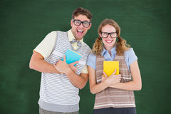 A Composite image of geeky hipster couple holding books and smiling at camera Stock Images