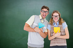 Composite image of geeky hipster couple holding books and smiling at camera Stock Photography