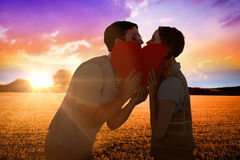 Composite image of geeky hipster couple kissing behind heart card Stock Photo