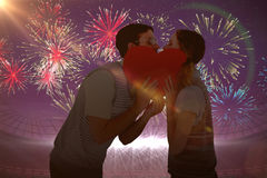 Composite image of geeky hipster couple kissing behind heart card Royalty Free Stock Photos