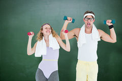 Composite image of geeky hipster couple lifting dumbbells in sportswear Royalty Free Stock Image