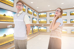 Composite image of geeky hipster couple looking at camera Royalty Free Stock Photo