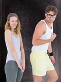 A Composite image of geeky hipster couple posing in sportswear Stock Image
