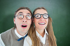 Composite image of geeky hipster couple raising eyes Stock Images