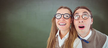 Composite image of geeky hipster couple raising eyes Stock Photos