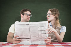 A Composite image of geeky hipster couple reading newspaper Stock Photography