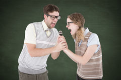 A Composite image of geeky hipster couple singing into a microphone Royalty Free Stock Photography