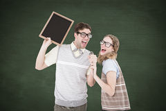 A Composite image of geeky hipster couple singing into a microphone Stock Image
