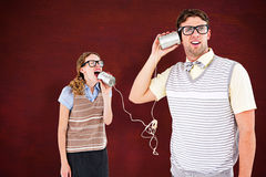 Composite image of geeky hipster couple speaking with tin can phone Stock Photos