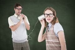 A Composite image of geeky hipster couple speaking with tin can phone Royalty Free Stock Photography