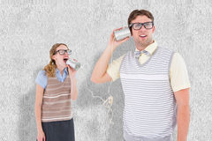 A Composite image of geeky hipster couple speaking with tin can phone Royalty Free Stock Image
