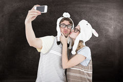A Composite image of geeky hipster couple taking selfie with smartphone Stock Photo