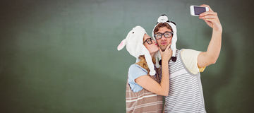 Composite image of geeky hipster couple taking selfie with smartphone Stock Image