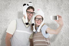 A Composite image of geeky hipster couple taking selfie with smartphone Royalty Free Stock Photo