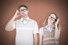 Composite image of geeky hipster couple thinking with hand on temple. Geeky hipster couple thinking with hand on temple against background Royalty Free Stock Photo