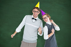 A Composite image of geeky hipster couple wearing a party hat Stock Images