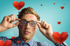 Composite image of geeky hipster covered in kisses Stock Photo