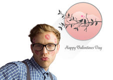 Composite image of geeky hipster covered in kisses Stock Photography