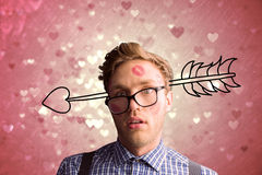 Composite image of geeky hipster covered in kisses Royalty Free Stock Photography