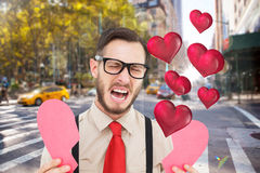 Composite image of geeky hipster crying and holding broken heart card. Geeky hipster crying and holding broken heart card against blurry new york street stock photos