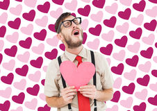 Composite image of geeky hipster crying and holding heart card Royalty Free Stock Photography