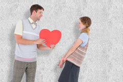 A Composite image of geeky hipster giving heart card to his girlfriend Royalty Free Stock Image