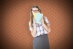 Composite image of geeky hipster hiding her face behind notepad Royalty Free Stock Image