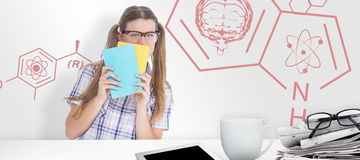 Composite image of geeky hipster hiding her face behind notepad Royalty Free Stock Photos