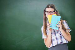 Composite image of geeky hipster hiding her face behind notepad Stock Image