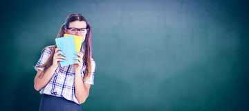 Composite image of geeky hipster hiding her face behind notepad Stock Images