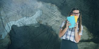 Composite image of geeky hipster hiding her face behind notepad. Geeky hipster hiding her face behind notepad  against rusty weathered wall Royalty Free Stock Photography