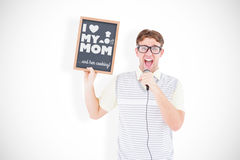 Composite image of geeky hipster holding blackboard and singing into microphone Stock Photography