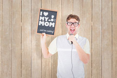 Composite image of geeky hipster holding blackboard and singing into microphone Royalty Free Stock Photo