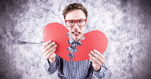Composite image of geeky hipster holding a broken heart Royalty Free Stock Photos
