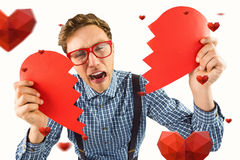 Composite image of geeky hipster holding a broken heart. Geeky hipster holding a broken heart against hearts stock image