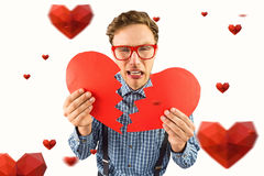 Composite image of geeky hipster holding a broken heart. Geeky hipster holding a broken heart against hearts royalty free stock image
