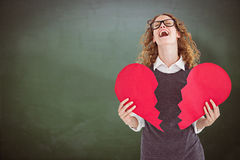 Composite image of geeky hipster holding a broken heart card Stock Images