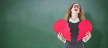 Composite image of geeky hipster holding a broken heart card Royalty Free Stock Images