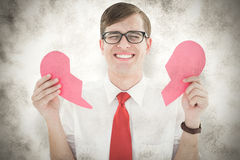 A Composite image of geeky hipster holding a broken heart card. Geeky hipster holding a broken heart card against grey background Royalty Free Stock Image